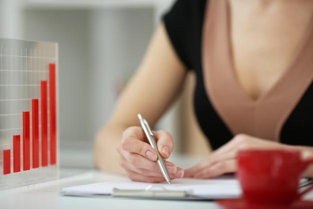 Женская рука с ручкой на листе бумаги на фоне графики. с глубиной резкости изображения