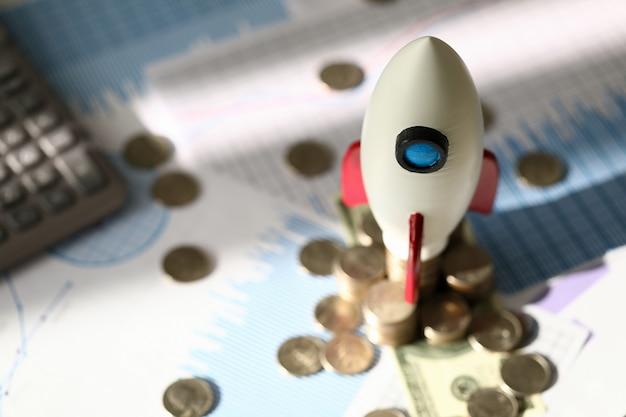 おもちゃの宇宙ロケットは電卓の近くのコインの上に立つ