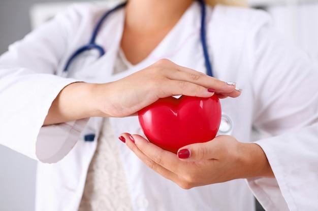 女医は腕で保持し、赤いハートをカバー