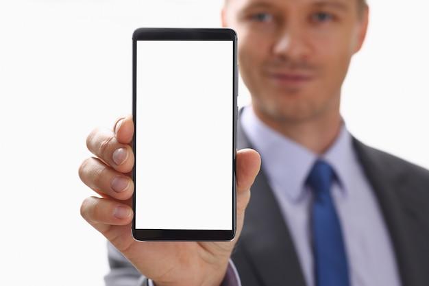ビジネスマンは彼の手で新しいスマートフォンを保持します