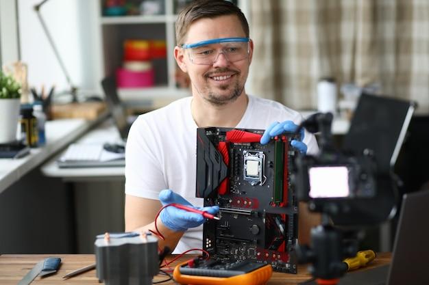 Мужчина снимает видео-блог о ремонте компьютеров камеры