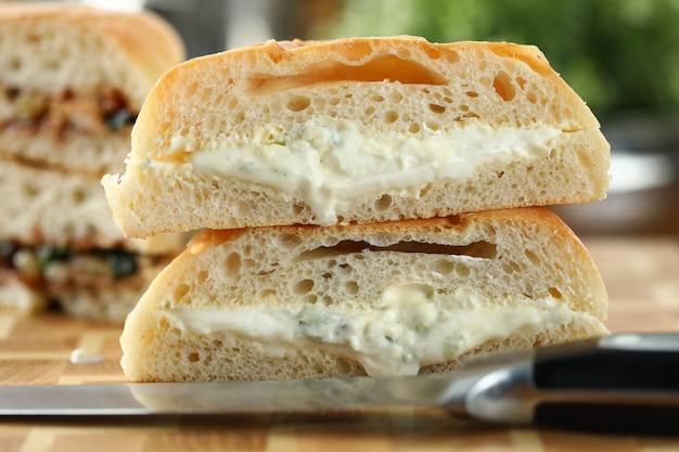Вкусный бутерброд с расплавленным сыром на фоне деревянной доске крупным планом.