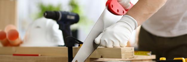 手袋をはめた大工は、横のこぎりで固定した部分を使用します。作成木材の幅広い質量とユニークな製品。貴重な木材からユニークなアイテムを作成します。マニュアル製造のドアと家具