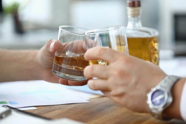 男性は職場に座って、眼鏡からアルコールを飲む
