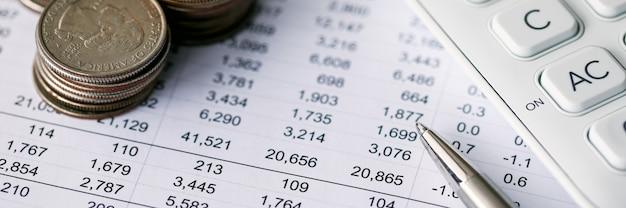 予算の増減のクローズアップ。費用の詳細な会計を伴う文書報告書。テーブルの上の現金お金の階段。電卓とペン。ファイナンスの概念