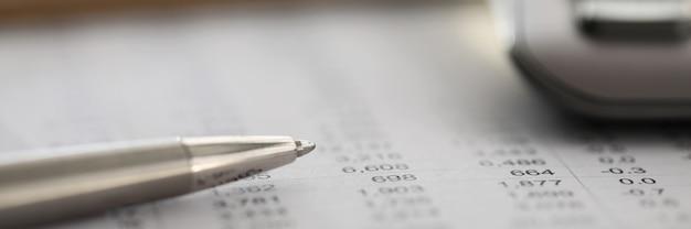 財務報告書の上に横たわる銀のペンのクローズアップ。列に数字が表示された毎月の夏。データの増減に関する統計。金融と経済の概念