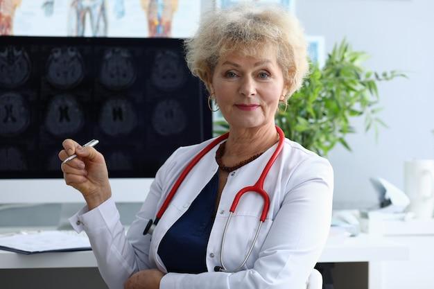 医者の女性は、ペンを背景に保持しています。