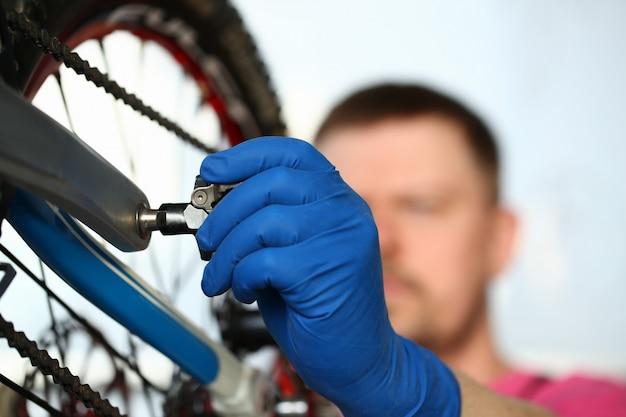 男は修理自転車のメカニズムを検査し、調整します