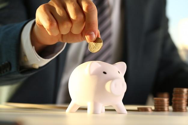 Рука бизнесмена положить деньги в свинью