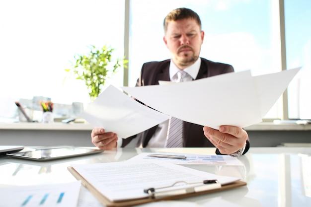 男性の腕は、オフィス職場のクローズアップで論文を保持します。