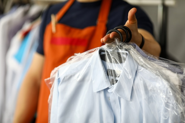 Служащий химчистки одежды возвращает рубашки клиенту