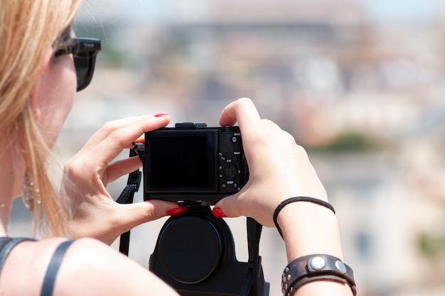 旅行写真のクローズアップをしようとしている小さなデジタルカメラを保持している女性