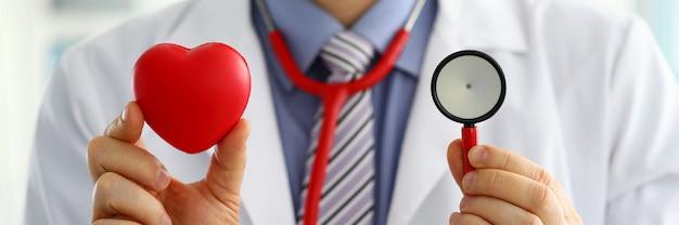 胸のクローズアップの前に赤いハートと聴診器の頭を保持している男性医学博士。医療ヘルプ循環器ケア健康予防予防保険手術と蘇生の概念