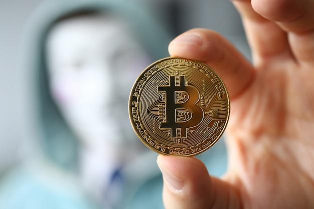 ハッカーは匿名マスクを着用し、ビットコインを手に持つ
