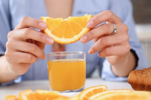 オレンジ色のスライドとジュースのグラスを保持する女性の腕