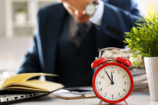 赤い目覚まし時計が遅い時間のクローズアップを示しています