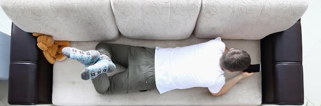 男はソファに横になり、現代のスマートフォンを手に保持