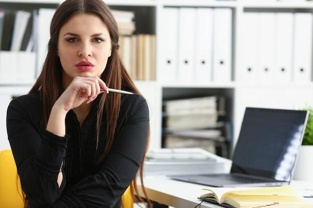 Красивая улыбающаяся девушка на рабочем месте держит серебряную ручку