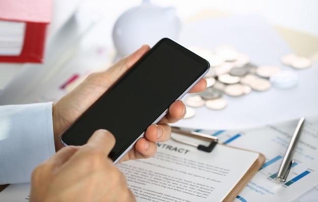 ビジネスマンは新しいスマートフォンを保持しています