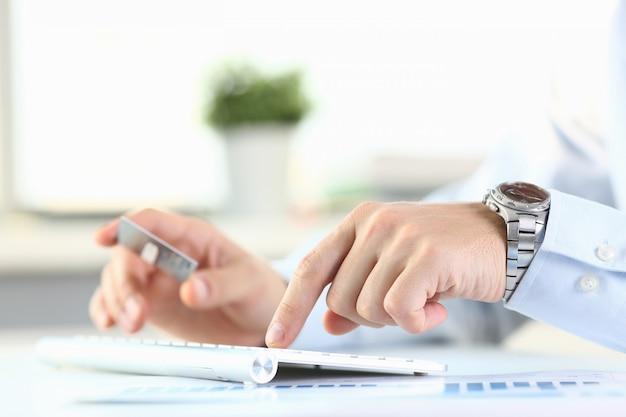 男性の腕はクレジットカードのプレスボタンを保持します。