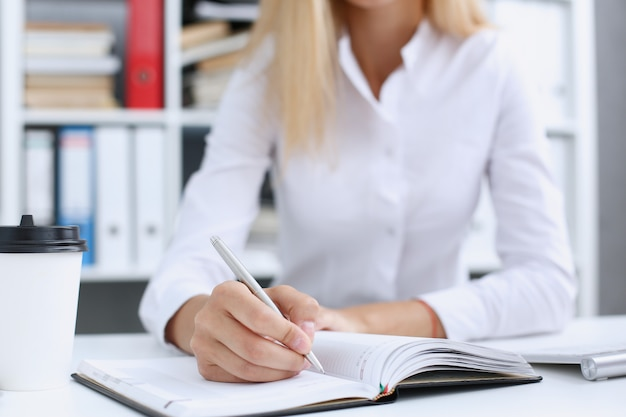 銀のペンを作る準備ができている女性の手