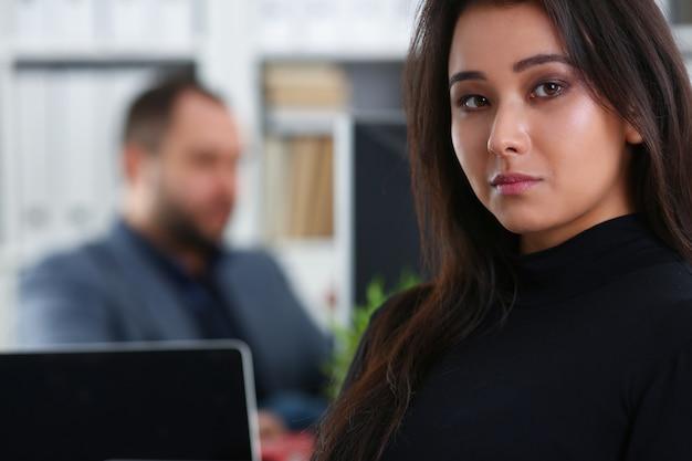 彼女の上司のキャビネットのオフィスのテーブルに座っている若い美しいブルネットの女性