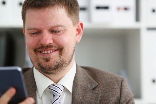 ハンサムな笑みを浮かべて実業家話携帯電話