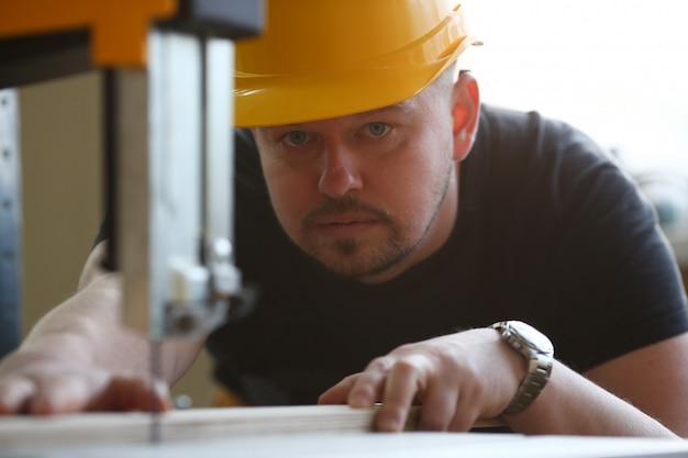 Рабочий, использующий портрет электрической пилы