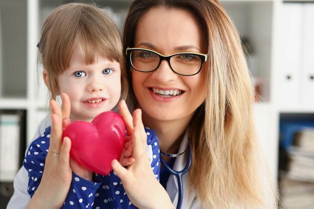 Женщина-врач и маленький ребенок держат в руках