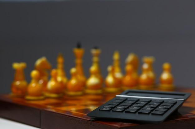 Черный калькулятор лежит на шахматной доске