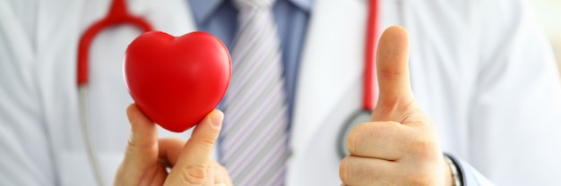 Мужской доктор медицины держит красное игрушечное сердце и показывает ок
