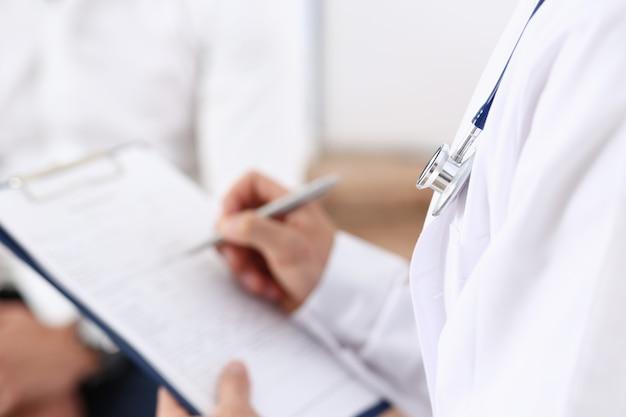 男性医師の手が患者の病歴リストを満たす銀のペンを保持