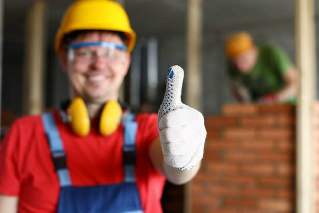 Счастливый улыбающийся мужской работник показывает палец вверх жест крупным планом. прекрасный ремонт дома или лучшая концепция обслуживания подрядчиков