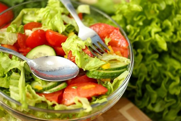 Серебряная вилка в тарелке смешивает салат со свежими овощами