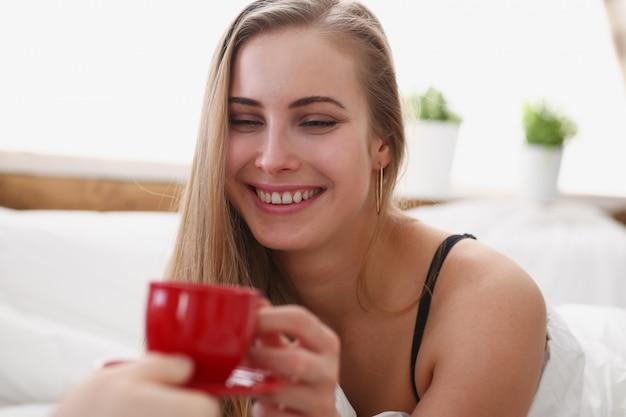 Блондинка пьет чашечку кофе рано утром в своей постели