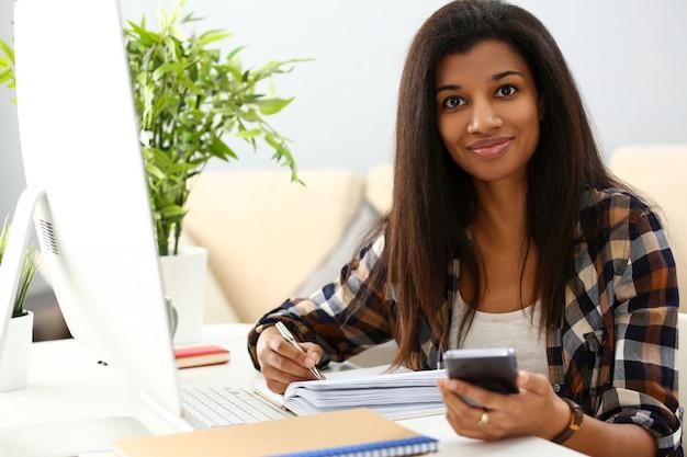Черная усмехаясь женщина сидя на рабочем месте писать что-то