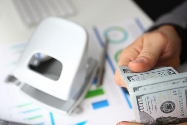 Бизнесмен рассматривает наличные доллары в офисе