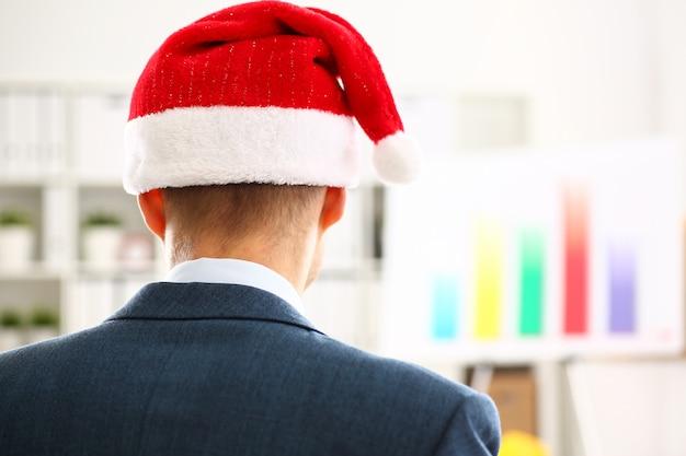 伝統的な赤い帽子をかぶっているスーツを着た男