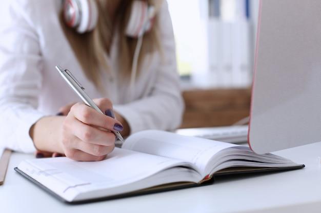 Женские руки делая примечания с серебряной ручкой пока работающ на крупном плане пк компьютера.
