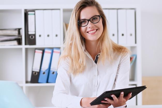 Красивая деловая женщина в очках портрет в офисе, держа планшет
