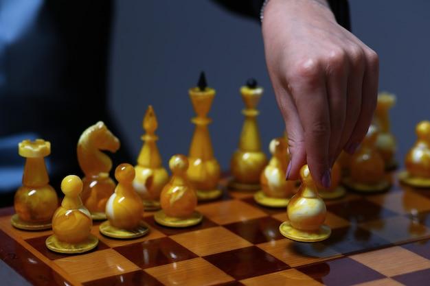 チェスの駒を保持しているビジネスの女性を持っている女性の手。