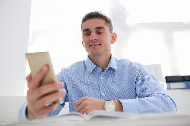 実業家は彼の手で新しいスマートフォンを保持しています。