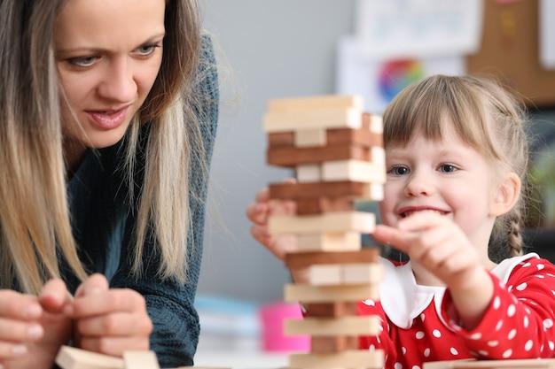 Мама и дочка укладывают блоки друг на друга