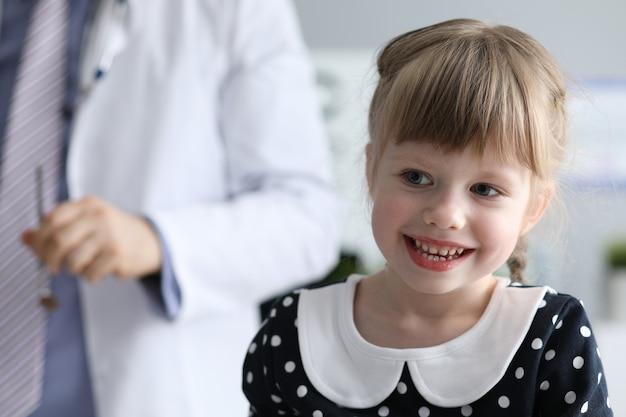 Здоровая маленькая девочка сидит в кабинете врача