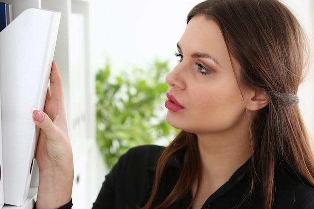 Красивая брюнетка женщина-клерк ищет нужный документ