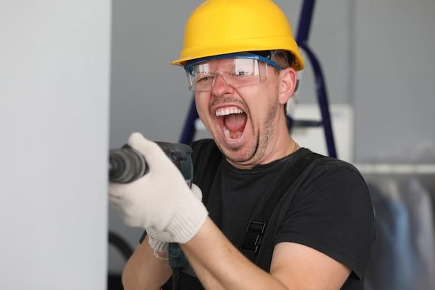 Мужской строитель в каске сверлит стену и кричит