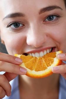 美しいブルネットの笑顔の女性はスライスしたオレンジを食べる