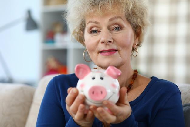 Счастливая пожилая женщина показывает розовую керамическую копилку