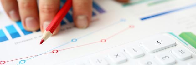 グラフィックの赤鉛筆とチェックポイントを持っている人の手のクローズアップ。デスクトップ上の電卓。会計結果のマクロ撮影。ビジネスと財務報告の概念