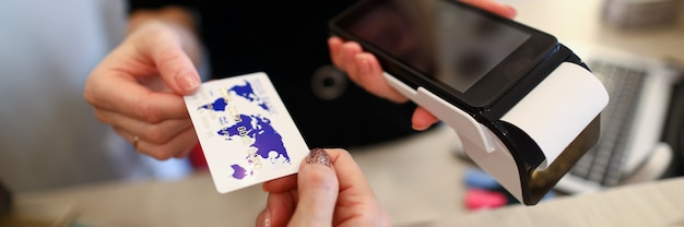 Крупный план продавца, принимая пластиковую кредитную карту от клиента для оплаты через терминальный сервер. код клавиатуры с экраном для информации и проверки. современная концепция технологии